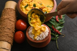 Prawn mango curry recipe and rice Chemmeen Manga shrimp in coconut milk. Spicy Kerala fish curry on dark black background South India. Top view popular Indian seafood, non veg food side dish for appam