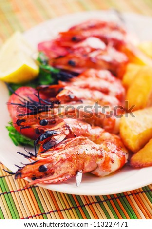 Prawn skewer with a side of baked potatoes (selective focus)