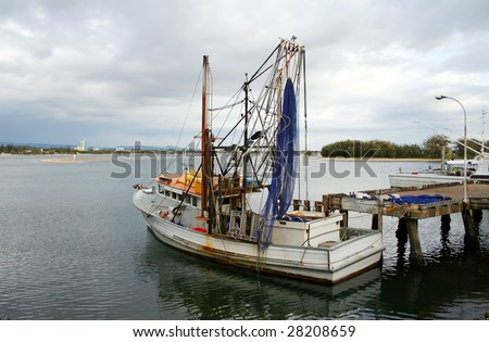 Prawn trawler sits at dock on an overcast day.