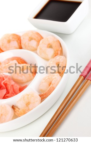 Prawns on plate with chopsticks and sauce isolated on white - stock photo