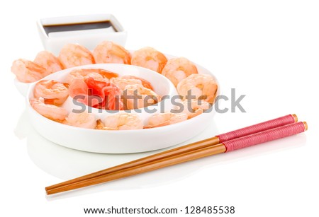 Prawns on plate with chopsticks and sauce isolated on white