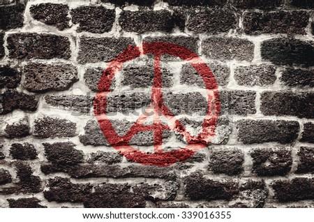 Pray for Paris, France - Red peace symbol graffiti on grunge brick wall
