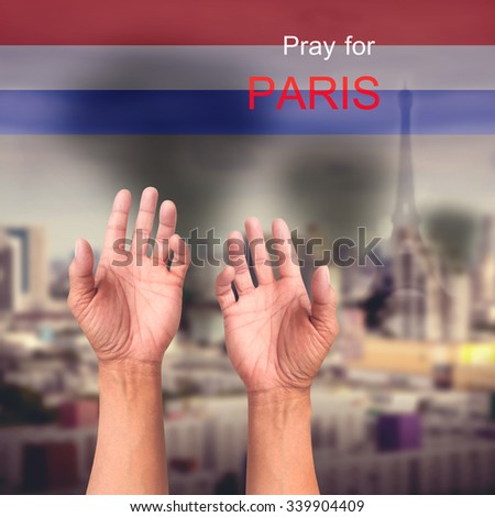 Pray for PARIS praying hands over explosion city on November 13 2015 and many people were killed across Paris with explosions attack