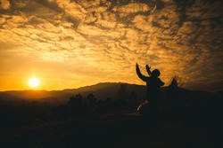 Pray of man kneeling down and lift hands at sunset background. christian silhouette concept.