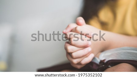 pray worship online at home.home church worship in sunday service.kid child girl hand praying and bible study.hope, faith, trust in GOD.Worship christian before bible study at home, close up hand pray