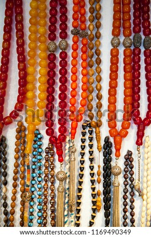 Prayer beads, rosary, in many different colors, hanging on the wall #1169490349