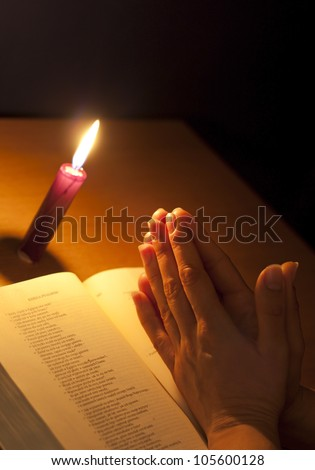 Prayer bible and candle in night meditation concept