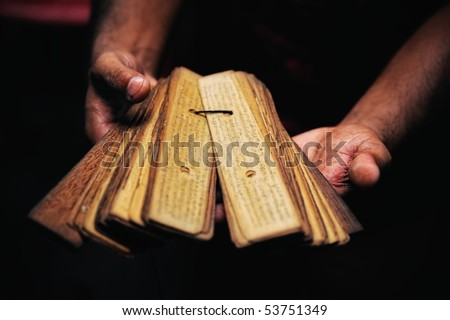 Prayer book of papyrus in the hands of Buddhist monk - stock photo