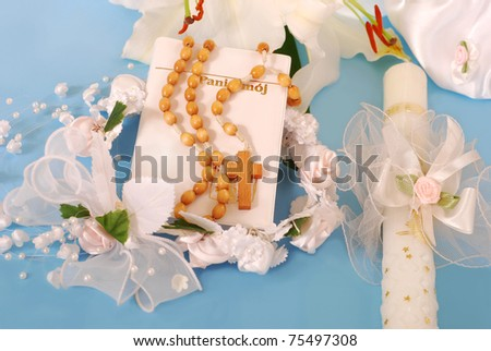 prayer book , wooden rosary and candle for first holy communion on blue background