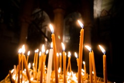 Prayer burning candle sticks in Holy Sepulchre Church in Old City Jerusalem, Israel
