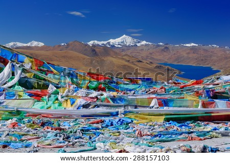 Prayer flags on Kamba La-pass over the 638 km2-130 km.E\'W-70 km.N\'S wide-4441 ms.high-turquoise colored Yamdrok Tso-Upper Pasture lake and 7206 ms.high mt.Nojin Kangsang. Lhoka or Shannan pref.-Tibet.