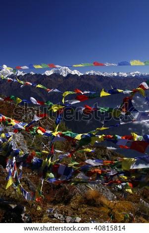 Prayer flags with mountain views from the top of yangrima peak - Helembu, Nepal