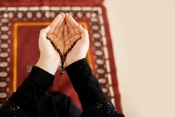 Prayer hands of a woman holding a rosary, with space for text