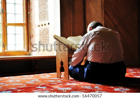 Prayer in mosque reading Koran