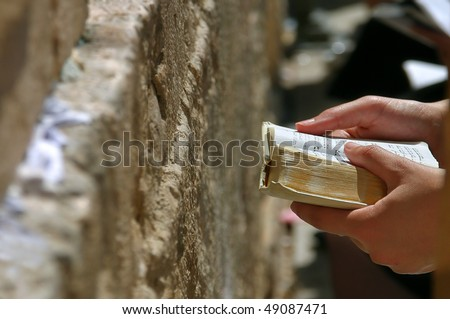 Prayers hands with Torah Book during prayer at Western Wall in Jerusalem, Israel.