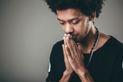 Praying african american man hoping for better. Asking God for good luck, success, forgiveness. Power of religion, belief, worship. Holding hands in prayer, eyes closed.