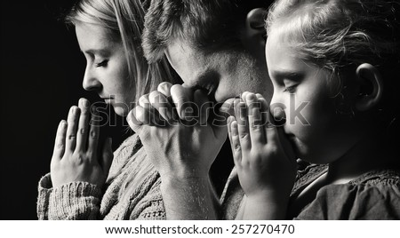 Praying family. Man, woman and child. MANY OTHER PHOTOS FROM THIS SERIES IN MY PORTFOLIO.