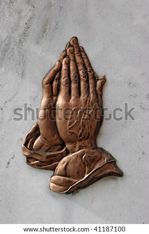 praying hands embossed on a marble plaque
