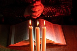 Praying hands next to bible. Man praying while reading the Bible. Crossed fingers next to book as a symbol of faith in God. Church candles in front of a praying person. Prayer hands close up.