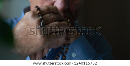 Praying hands of an old man holding rosary beads. #1240115752