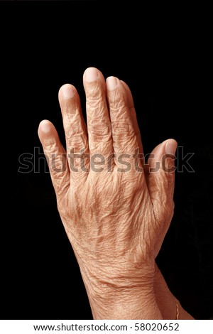 Praying hands of an old woman - stock photo