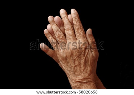 Praying hands of an old woman