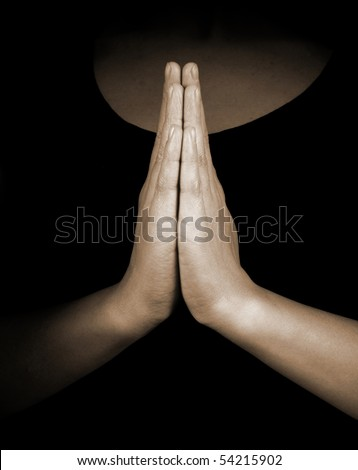 Praying hands on black background