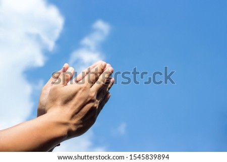 Praying hands on blue sky background,Young man prayed,Religion and spirituality with believe