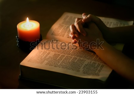 Praying hands on top of open bible, lit only by candle light - stock photo
