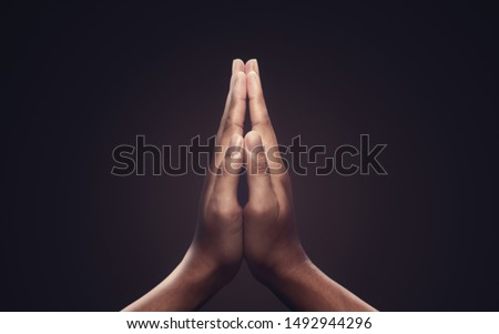 Praying hands with faith in religion and belief in God on dark background. Power of hope or love and devotion. Namaste or Namaskar hands gesture. Prayer position. Stockfoto ©