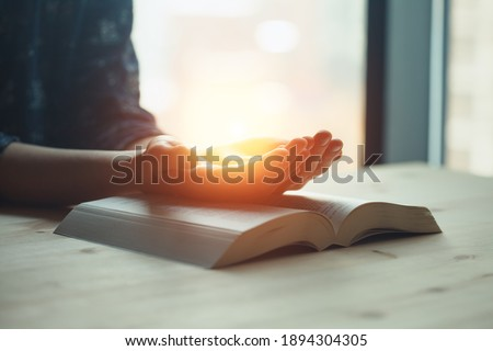 praying hands, young woman prayer  with hands together over a Holy Bible, spiritual light, mind and soul peace Photo stock ©