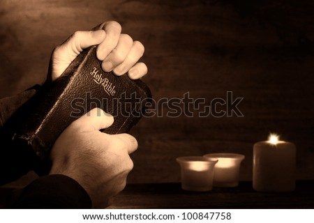 Praying man hands holding and clinching an old holy bible sacred book in a dark church during a prayer worship service with religious candles glowing in nostalgic aged sepia