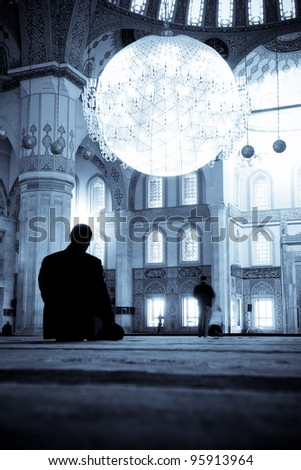 Praying Muslim man silhouette in Kocatepe Mosque Ankara Turkey Split toned