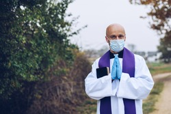 Praying priest in a protective mask and protective gloves somewhere on the road