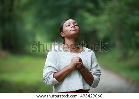 praying to god, posing african, american black, girl adult fashionable model, feeling moments, enjoying, happiness #493429060