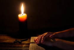 Praying woman hands on old holy bible sacred book in a dark church during a prayer worship service with religious candles glowing, religion and faith concept