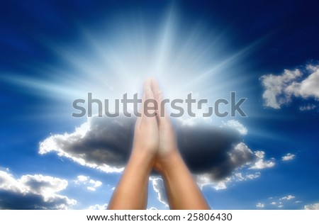 praying woman over blue sky with rays of light