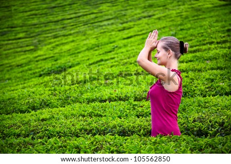 Praying woman with hands in namaste in red cloth on tea plantations in Munnar hills, Kerala, India