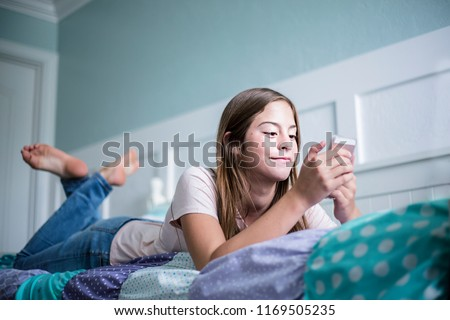 Pre-adolescent teen girl texting on a smartphone lying in bed at home. Candid indoor photo withFocus on the foreground and copy space #1169505235