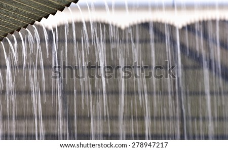 Pre-Monsoon Summer rains in May in Kerala, India. Copious amounts of water run drown from the rooftop. Rainwater harvesting is a wise way to prevent wasting water.