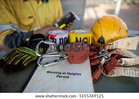 Pre operation safety workplace working at heights permit book on the table defocused an inertia reel shock absorbing fall protection device with danger caution tags hard hat gloves alcohol tester    Stockfoto ©
