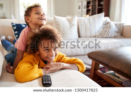 Pre-teen African American girl lying on sofa watching TV in the living room with her younger brother sitting on her back, close up