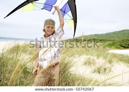 Pre-teen boy arms raised, holding kite above head on beach
