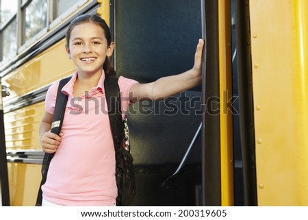Pre teen girl getting on school bus - stock photo