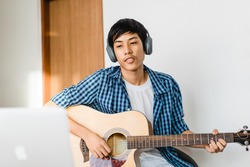Pre teens boy 15 years old play guitar sing a song and worship in sunday service live streaming video.Online learning music.Lockdown at home.Influencer asian handsome teenager boy practice guitar.