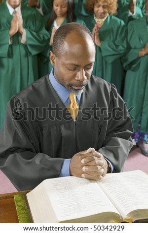 Preacher by altar in church Bowing Head in Prayer, high angle view
