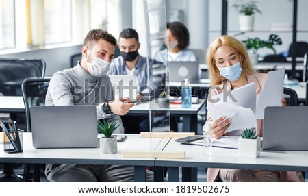Precautions and social distancing in coronavirus pandemic. Millennial guy and girl in protective masks discussing and working with documents in workplace in office, panorama