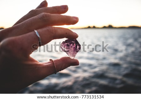 Precious Amethyst crystal, held onto tightly between a young girls fingertips. Such gemstones are essential tools when delving into witchcraft.
