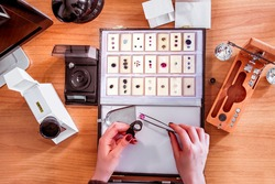 precious gem stones appraisal, a gemologist examines a ruby using tweezers and evaluating gemstones  top view of gem specialists hands while at work holding magnifier loop  and gemological instruments