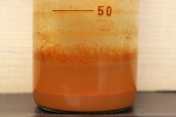 Precipitation of an orange insoluble iron compound in a beaker.